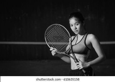Young woman holding tennis racket on black
