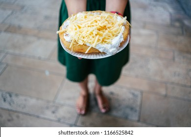 A young woman holding a traditional Hungarian Langos with cheese, Budapest, Hungury