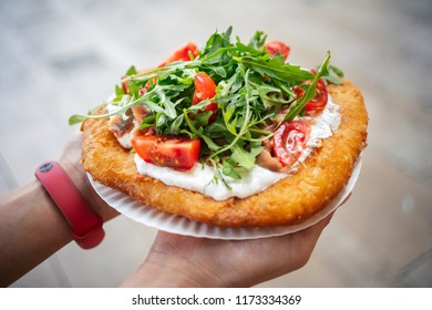A young woman holding a traditional Hungarian Langos with cheese, rucola and tomatoes , Budapest, Hungury