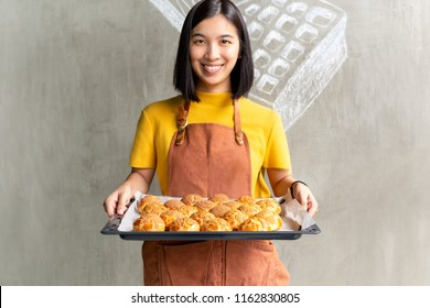 Young woman holding tray with fresh Choux cream or eclair
