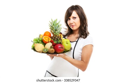 Young woman holding a tray with fresh fruits - apples, pears, grapes, pineapple, oranges, kiwi, strawberries and others.