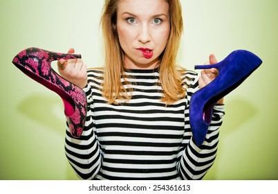 Young woman holding two different shoes wondering which one to wear.