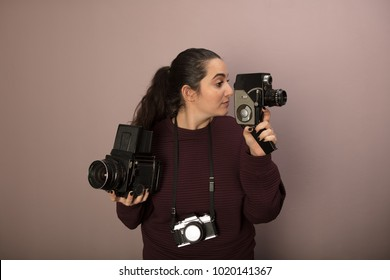 Young woman holding two vintage cameras, one for stills, one for video, with a small compact hanging around her neck in a concept of photography as a hobby, collectibles or being a photo boffin