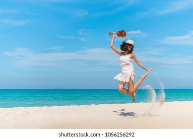 Young woman holding ukulele and jumping on beach with happy. Summer vacation with blue sky in sunny day. Freedom life.