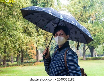 Young woman holding umbrella in a park during rainy day. Female with face mask for city life in the green