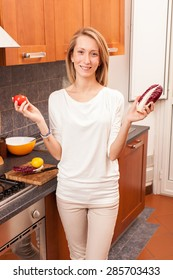 Young Woman Holding Vegetables in the Kitchen