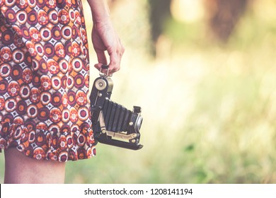 Young woman holding a vintage camera outdoors. Nostalgia concept. (Retro toned image with selective focus)