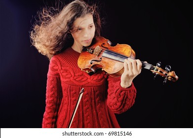 Young woman holding a violin. Isolated on the black background