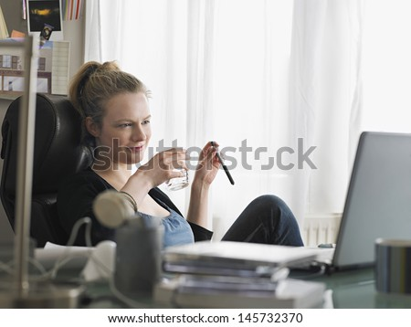 Young woman holding water glass while looking at laptop in home office