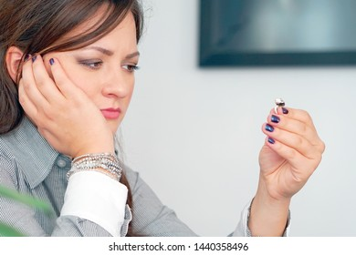 A young woman holding wedding engagement ring in hands, engaged girl doubts about marriage proposal, abandoned wife depressed after getting divorced, help to overcome breaking up, starting new life