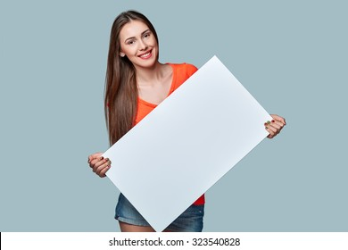 Young woman holding white blank cardboard, over gray background.