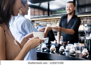 Young woman holding a white cup of coffee next to her partner served by a friendly barista in a modern coffee shop