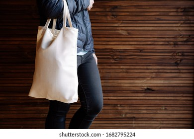Young woman holding white textile eco bag on wood background