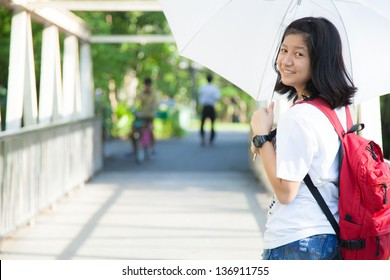 Young woman holding a white umbrella. In the middle of a bridge over the river in the park.