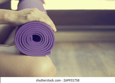 Young woman holding a yoga mat, vintage style