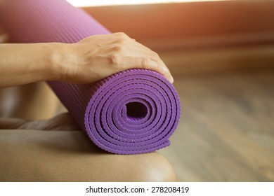 young woman holding a yoga mat among flare light
