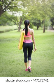 Young woman holding a yoga mat to fitness at garden