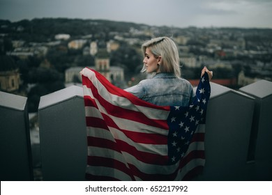 Young woman holds an American flag against city background. Back view.