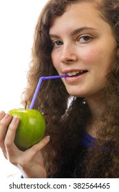 A young woman holds an apple in her hand and drinks with a straw therefrom