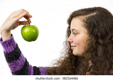 A young woman holds an apple in her hand and smiles