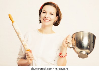 A young woman holds a bowl from a mixer and a rolling pin in flo
