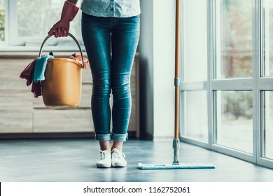 Young Woman holds Bucket with Cleaning Equipment. Closeup of Beautifull Girl wearing Gloves holding Bucket with Cleaning Supplies ready to start Cleaning Apartment. Woman preparing to Clean - Shutterstock ID 1162752061