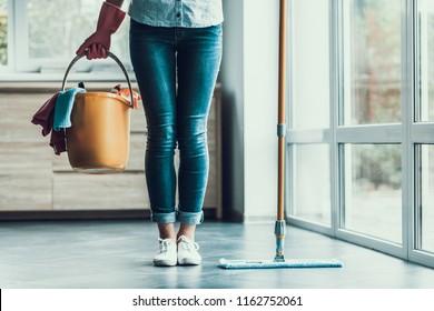 Junge Frau hält Eimer mit Reinigungsgerät. Nahaufnahme von Beautifull Girl mit Handschuhen, die einen Eimer mit Reinigungsmitteln tragen, die bereit sind, die Reinigungswohnung zu starten. Frauen, die sich auf Sauberkeit vorbereiten