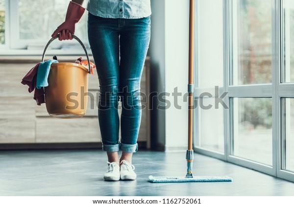 若い女性は掃除用具を持ってバケツを持つ。掃除用具と手袋を持つ美人の女の子の接写で、アパートの掃除を始める。掃除の準備をしている人