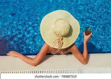 Young woman holds a cocktail in the swimming pool