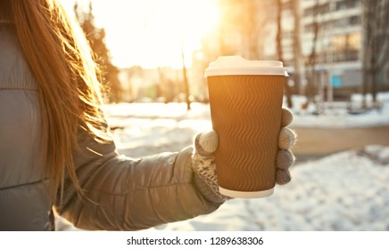 Young woman holds cup of coffee takeaway in the winter park