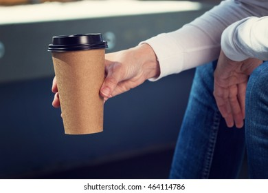 Young woman holds disposable brown paper cup of coffee. Copy space on cup.