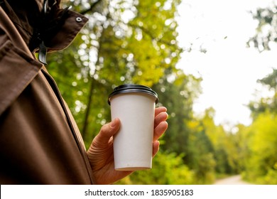 Young woman holds a disposable cup of coffee on on a sunny morning or day. Woman going for a walk with a cup of coffee on beautiful autumn day.