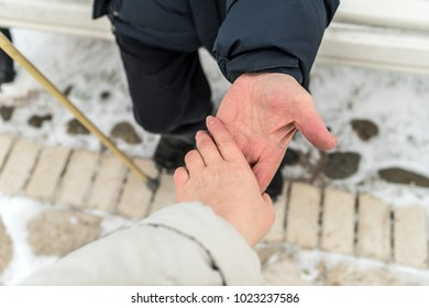 A young woman holds an elderly man by the hand. Retired with a wand. Winter, day.