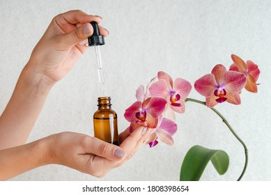 Young woman holds an essence for skin in her hands. Tropical orchid flowers. Unisex cosmetics. Place for  text.  Spa natural organic products. Anti-age cosmetics for men and women.