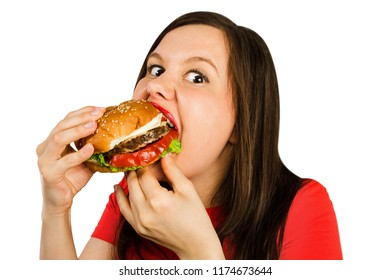 Young woman holds hamburger and with appetite eats him, isolated on white background. Looks in camera.