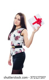 The young woman holds in hand a gift with a red bow and smiles