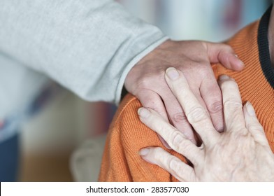 Young woman holds a hand on the shoulder of a senior citizen.