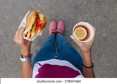 Young woman holds in hands a paper cup with tea and a hamburger. View from above. Fast food concept
