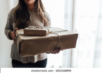 Young woman holds in hands stacked Christmas gift boxes in craft paper with juniper. Christmas presents concept.