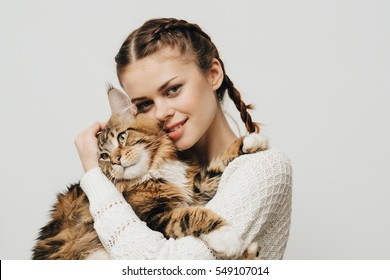 Young woman holds in her arms and hugs Maine Coon cat. White background