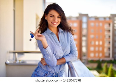 Young woman holds the keys of the apartment in her hand