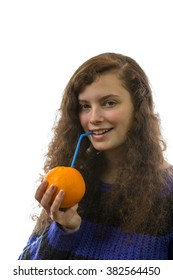 A young woman holds an orange in her hand and drinks with a straw therefrom
