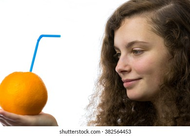 A young woman holds an orange in her hand and smiles