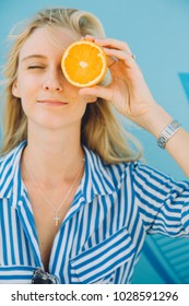 Young woman holds an orange near her eye