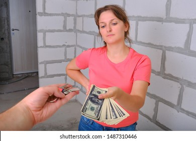A young woman holds out money to exchange for the keys to the new house. A deal to buy and sell a newly built apartment. American dollars in exchange for new housing.