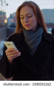 Young woman holds a phone in her hand on the street
