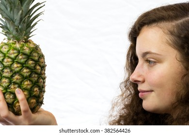 A young woman holds a pineapple in her hand and smiles