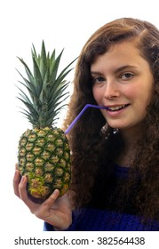 A young woman holds a pineapple in her hand and drinks with a straw therefrom