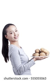 young woman holds a plate of potatoes