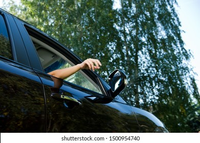 A young woman holds a relaxed arm outside the car - sticking her hand out through the open window of the front seat of a dark car. View from below, on the background of blurry trees and sky